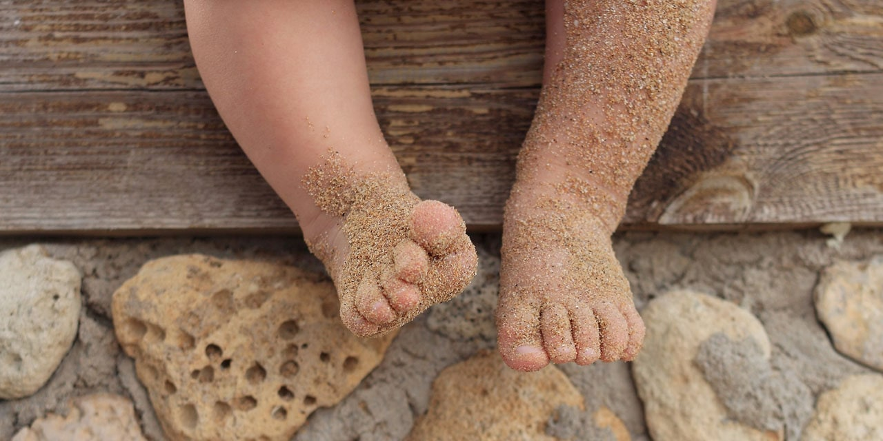 Feet in sand at the beach